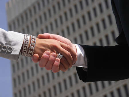 A businessman and a businesswoman shake hands with office building out of focus in background.