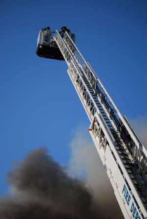 Ladder truck with fireman at top battles a blaze. Imagens