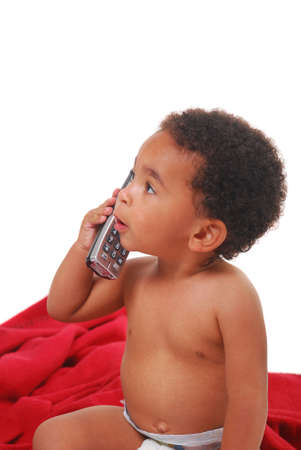 phone button: A multi-racial baby boy wrapped in a red blanket playing with a telephone.