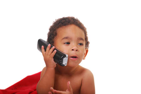 A multi-racial baby boy wrapped in a red blanket playing with a telephone. photo