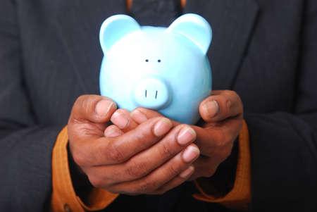 cradling: African-American male hands cradling a piggy bank.