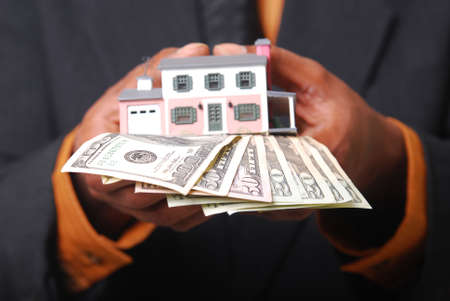 sold small: African-American male hands holding a miniature house and American currency. Stock Photo