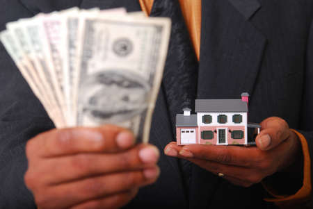 African-American male hands holding a miniature house and American currency. Shallow DOF with focus on house.