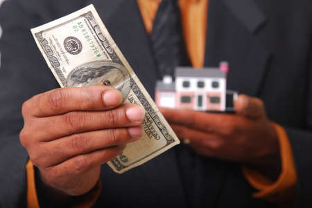 sold small: African-American male hands holding a miniature house and American currency. Shallow DOF with focus on bills.