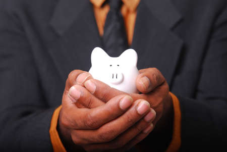 African-American male hands cradling a piggy bank. Stock Photo - 3728736
