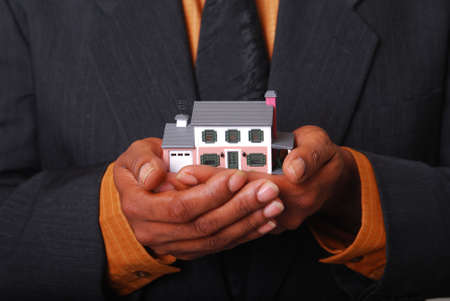sold small: African-American male hands holding a miniature house.