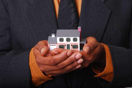 sold small: Afro-americano di sesso maschile in possesso di un mani in miniatura casa.