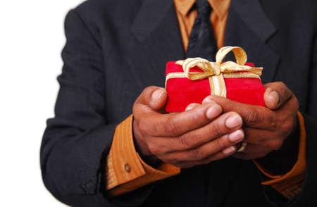 dar un regalo: Afro-americanos de sexo masculino manos la celebraci�n de una caja de terciopelo rojo con cinta de oro.