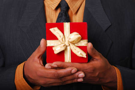 africanamerican: African-American male hands holding a red velvet box with gold ribbon.