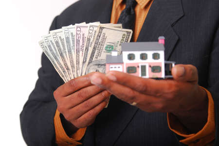 sold small: African-American male hands holding a miniature house and American currency. Shallow DOF with focus on money. Stock Photo