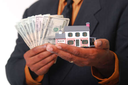 sold small: African-American male hands holding a miniature house and American currency. Shallow DOF with focus on house.