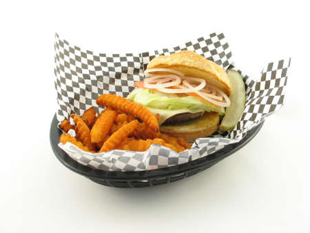 diner style burger with sweet potato fries in a basket over white