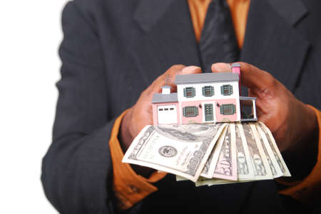 African-American male hands holding a miniature house and American currency. Shallow DOF with focus on money. Stock Photo