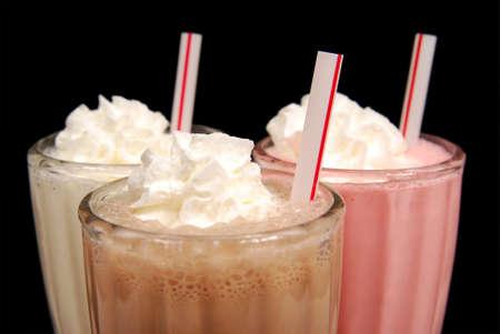 three milkshakes with whipped cream against black 写真素材