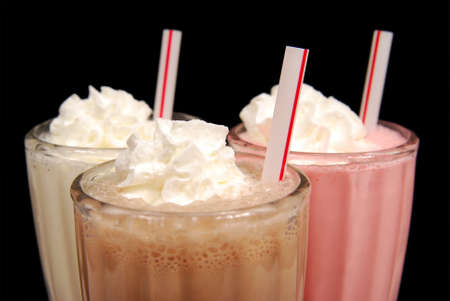 three milkshakes with whipped cream against black Stock Photo
