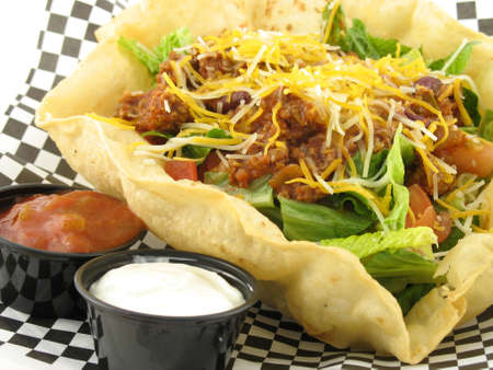 close up of taco salad with beef in a taco shell bowl with salsa and sour cream on side Stock Photo