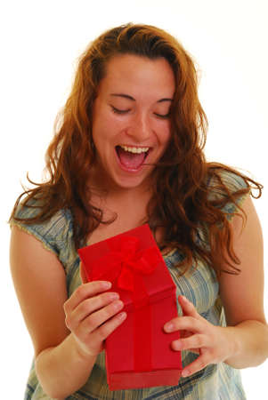 Beautiful woman opening a red gift with happy surprised expression. Stock Photo - 4872838