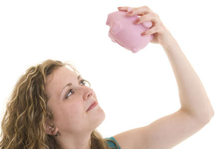 Attractive Caucasian woman looking up into piggy bank. photo