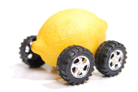 A lemon with wheels representing a defective vehicle. Shallow depth of field focus on fron wheel and front of lemon. Stock Photo