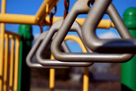 handhold: Climbing toys at a playground against a blue summer sky. Shallow depth of field focus on second hand-hold.