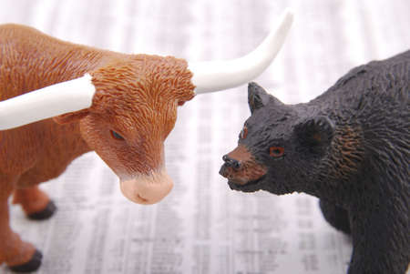 Miniature bull and bear on out of focus stock market report.