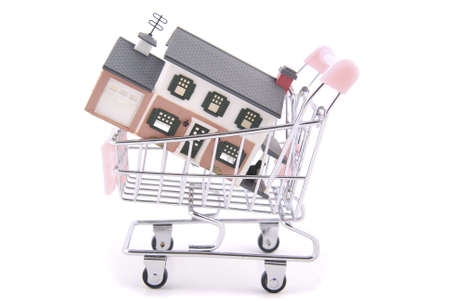Miniature house in miniature shopping cart symbolizing home shopping. photo