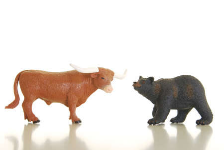 Miniature bull and bear photographed on white symbolizing financial markets