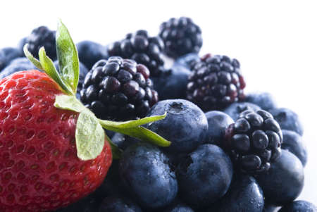 Pile of fresh blueberries and blackberries with a single strawberry on top. photo