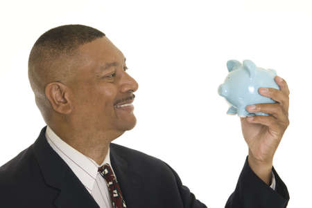 retiring: African American businessman holding a piggy bank isolated on white.