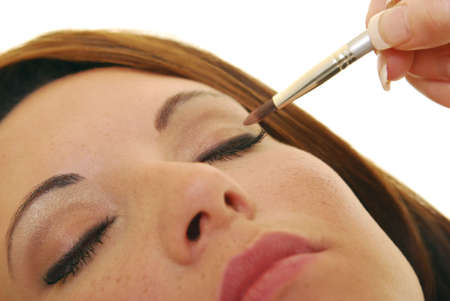 Close up of an attractive woman having makeup applied.