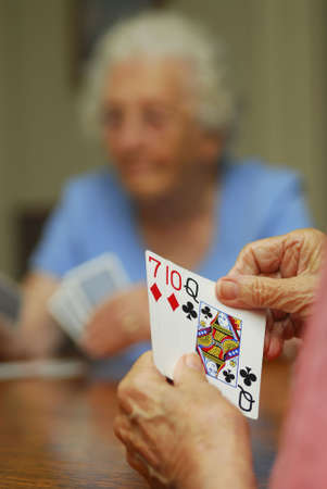 woman holding card: Elderly woman playing cards. Shallow depth of field. Focus on hands holding cards.