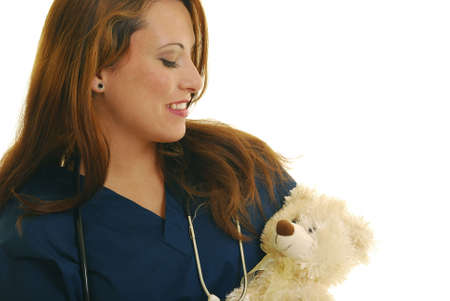 Attractive Caucasian nurse holding stuffed animal.