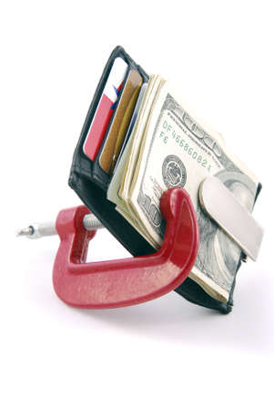 stingy: Wallet with cash and credit cards squeezed in a clamp.