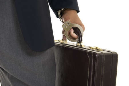 African American male hand holding a briefcase while handcuffed to it.