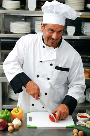 Attractive Caucasian chef cutting fresh vegetables in a restaurant kitchen.