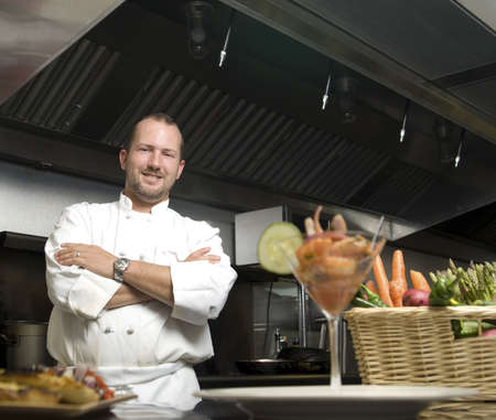 Attractive Caucasian chef standing with arms crossed in a restaurant kitchen. photo