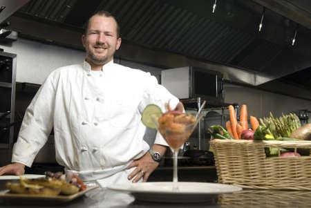 魅力的な白人シェフの野菜のバスケットのレストランのキッチンに立っています。