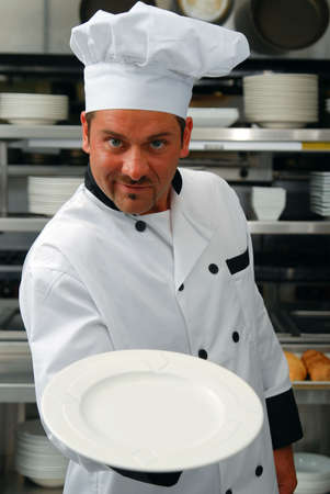 plate: Attractive Caucasian chef holding an empty plate in a commercial kitchen Stock Photo