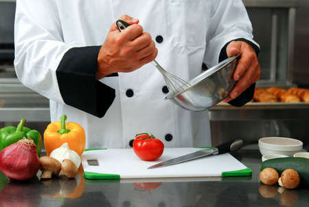 Caucasian chef mixing something in a bowl with fresh vegetables on a cutting board in front of him in a restaurant kitchen. Stock Photo