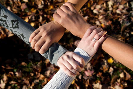 varying: Four teens of varying nationalities grasping each others wrists outdoors in the fall Stock Photo