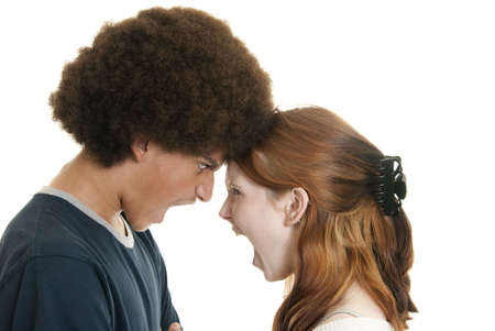 A cute Caucasian teenage girl and her mixed-race teen boyfriend yell at each other Stock Photo - 5852469