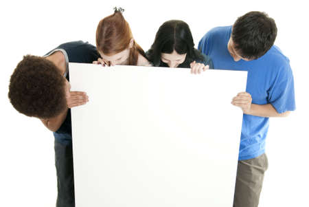 Four teenagers of various ethnic backgrounds holding and looking at a blank sign.
