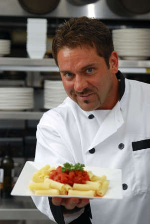 Attractive Caucasian chef holding a plate of pasta with red sauce in a restaurant kitchen.