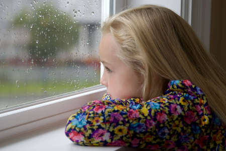 A young blond girl sits looking out the rainy window