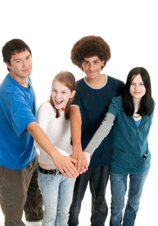 Four teens of different ethnic backgrounds with their hands together. Focus on hands