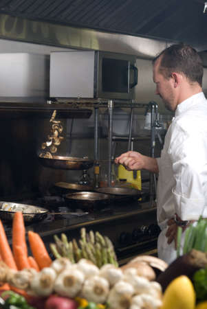 Caucasian chef in a smoky restaurant kitchen stirring mushrooms by flipping them into the air. Stock Photo
