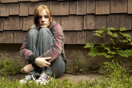 A teenage girl with a sad expression sits against a run-down house. photo