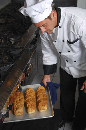 A Caucasian chef removes fresh loaves of bread from the oven in a commercial kitchen