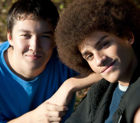 Two mixed-race teens pose for the camera on a sunny day