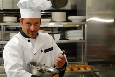 Attractive Caucasian chef mixing food in a bowl in a restaurant kitchen. Stock Photo